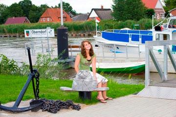 Eine Frau bei der Seehund-Statue beim Schiffsanleger in Oberndorf