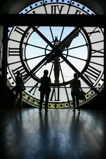 Silhouettes devant une immense horloge évoquant le temps