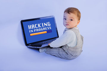 "Infant boy sitting with laptop computer resting on his legs and looking over shoulder at the camera. The screen has a yellow progress bar and the words ""Hacking in Progress""."