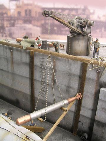 Die Torpedos werden zum Boot gehievt, die Beladung erfolgt wegen der drangvollen Enge des XXIII direkt außen über die Bugsektion, Nachteil: kein Nachladen während der Fahrt möglich.