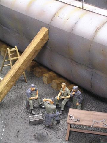 Werftarbeiter haben sich zur Skatrunde auf dem trockenen Dockgrund versammelt