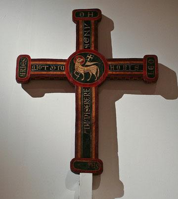 """Agnus Dei, Cordero de Dios.Cruz de Baguergue. Temple, relieves de estuco y restos de hoja metálica corlada sobre madera, procede del Valle de Arán. INSCRIPCIÓN: """"Oh AGNUS DEI QUI TOLLIS PECCATA MUNDI MISERERE NOBIS"""""""