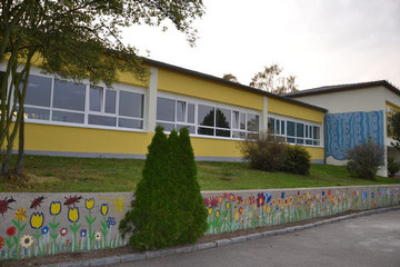 neue Fassade mit von Kindern bemalter Mauer