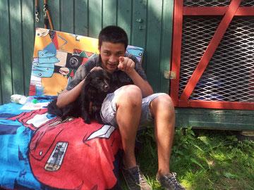 Jugendlicher mit schwierigem Hintergrund beim Kuscheln mit einem Hund