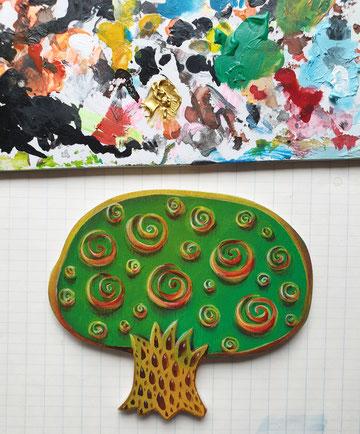 Ein dekorativer, kleiner Baum mit grüner Krone und Kringeln in gelb, orange, rot.