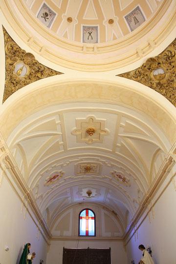 Detalle de la nave de fondo plano con boveda de medio cañón y la cúpula sobre pechinas. También se puede observar las cruces de la Orden de Santiago y las conchas en relieve que adornan el interior de la cúpula.