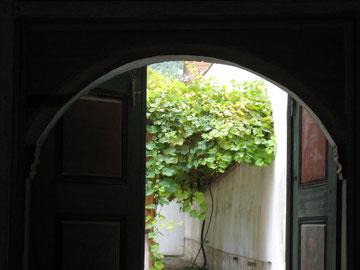Ein grünes Tor öffnet den Blick auf einen begrünten Hof.