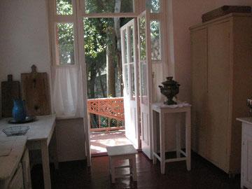 Die Küche von Tschechovs Gästehaus in Jalta - weißgestrichene Holztischchen und ein Blick nach draußen auf die grüne Terrasse