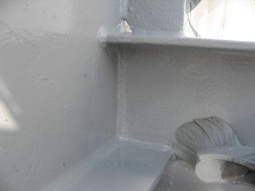 鉄製屋根の中塗りをハケで塗っている様子。