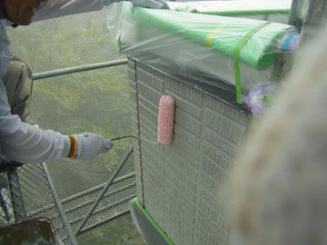サイディング外壁プライマーをローラーにて塗替えている様子。
