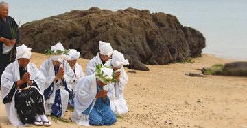 伝統行事のウンジャミ。アハシの海岸でナートゥンチビ(拝所)に向かって喜界島ノロの船出を見送る。岩の上で一斉に「オー 」の葉を海に投げ込み航海安全を祈る。 ※「オー」とはダンチクという暖地の海岸近くに生育するイネ科の多年草のこと。