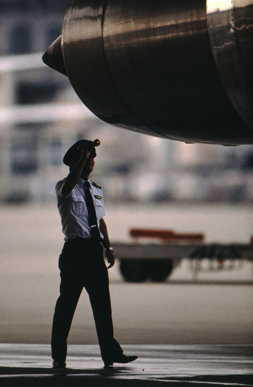 "A Japan Air Lines pilot doing his preflight ""walkaround"" inspection; Narita, Japan."