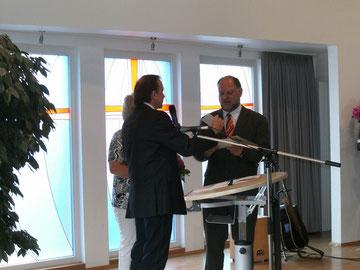 Der Gebietsvorstand Ernst Förster übergibt Markus als Abschiedsgeschenk einen Fahrschul-Gutschein