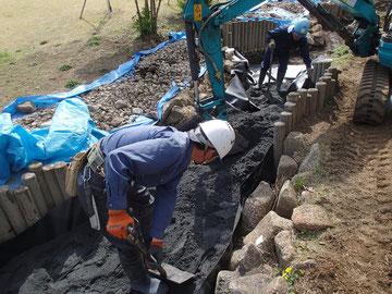 カーブした小川に対して、固くて重い材質の防水シートの設置に手こずりましたが、苦労の甲斐あって漏水が止まりました。