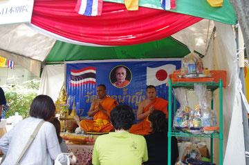 タイのお坊さんが祈祷、お経を唱える光景。在日タイ人、日本人もお寺のブースに。「第14回 タイ・フェスティバル2013年 東京・代々木」の会場写真