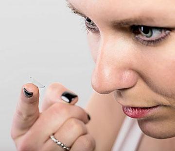 Foto: Frau beim Einsetzen der Kontaktlinse