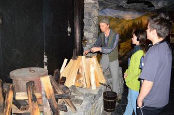 Die Kinder sehen zu, wie früher das wertvolle Steinöl gewonnen wurde