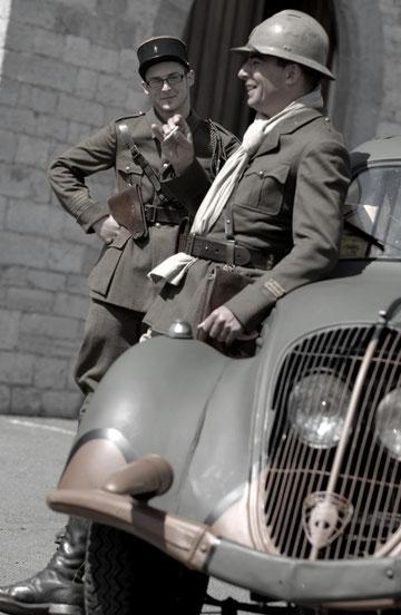 Adossé à une Peugeot 202 de 30 chevaux, modèle fabriqué de 1938 à 1949, ce lieutenant insouciant qu'un capitaine, comme lui, français, perce du regard...