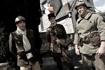 Ces deux mêmes officiers français posant plus sérieusement, en compagnie de leur estafette, et, tournant tous trois le dos au monument aux morts du village de Haut-le-Wastia