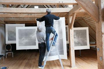 """Die """"Wolkenbilder"""" von Georges Wenger erhalten gerade ihren """"idealen"""" Platz im Dachgeschoß."""