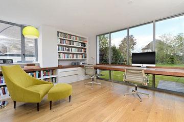 Despaho con sillón verde, sillas de escritorio, gran pantalla de ordenador y un ventanal con vistas a un gran jardín