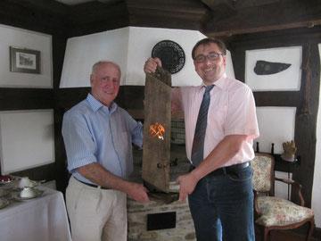 Willi Volk erhält vom Vorsitzenden der FWG/FBL Holger Puttkammer eine Lichtinstallation mit dem Zunftzeichen der Dachdecker.