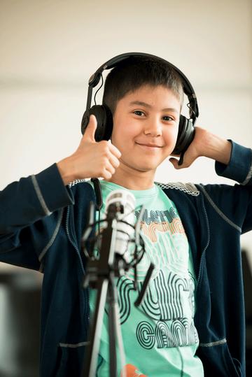 Bild von eiem Jungen mit Kopfhörern vor einem Mikrofon, der den erhobenen Daumen nach oben streckt.