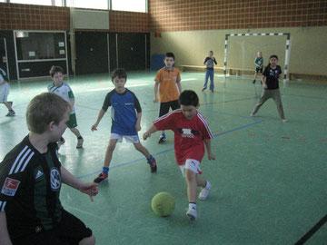 Der gelb-grüne Ball ist das begehrte Obhjekt: Mädchen und Jungen kicken ihn durch die Halle