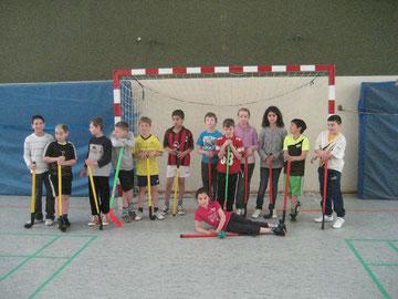 Gelbe und rote Hockeyschläger: Schülerinnen und Schüler mit den Sportgeräten vor dem sportlichen Vergleich