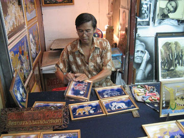 Glasmalkünstler Sayon Kaew-Lerng in seinem Stand auf dem Nachtbasar in Chiang Mai