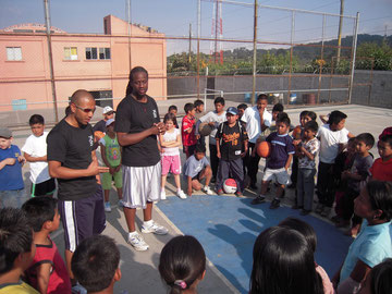 mynor & george teaching at a basketball camp in 2009