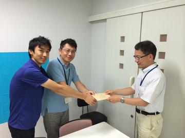 取りまとめてくださった石狩市役所のOB代表、13期・岩本隆行さんから募金を受け取る26期・工藤さん 6期・久保田さん
