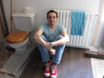 Eric pose du parquet dans une salle de bains.