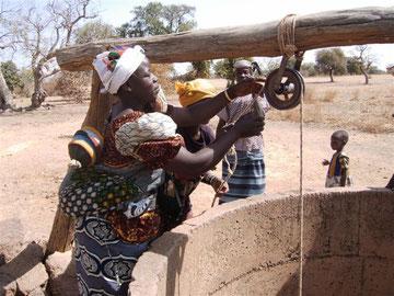 Femme tirant l'eau de l'ancien puits