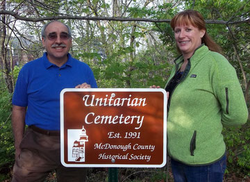 Heather McIlaine-Newsad (right), president of the board of the Unitarian Universalist Fellowship of Macomb, and Russell Hamm (left), treasurer, accepted the newest sign in the cemetery marking project sponsored by the McDonough County Historical Society.