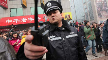 "A police officer disperses members of the public, most of them onlookers, and media outside a McDonald's after internet social networks called for a ""Jasmine Revolution"" protest in Beijing. (How Hwee Young / EPA / February 20, 2011)"