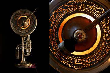 Assemblage light art sculpture made from a silver trumpet, a musical disc from a mechanical player, an oil can, top of a salt shaker, illuminated within a copper concave dish.