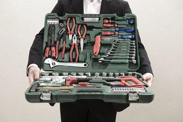 mann im anzug hält werkzeugkasten © jeremias münch