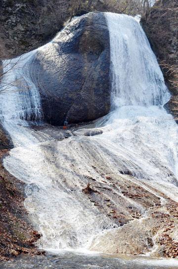 みろくの滝の頂上には、南祖坊が修行した台座がある。滝中央は筆者。