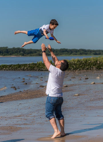 Familienfotos im Freien am Strand - Papa wirft Sohn in die Luft