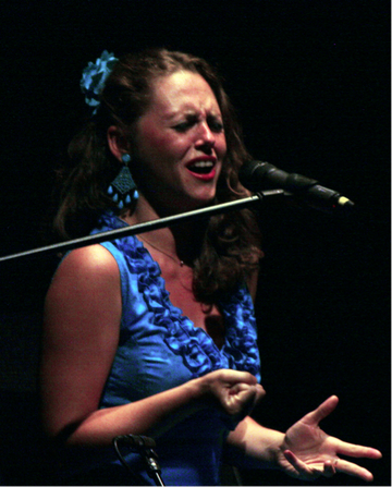 Zu sehen ist Felicia bei ihrem Auftritt in Stuttgart 2012. Sie trägt ein türkisblaues, ärmelloses Kleid, die Haare offen und hat eine türkisblaue Blume im Haar sowie türkisblauen Ohrschmuck.