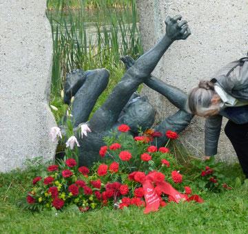 Ältere Teilnehmer legen Blumen am Mahnmal nieder -