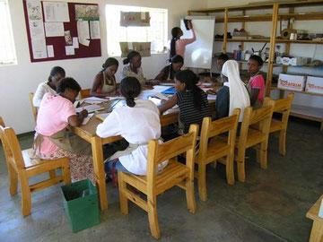 Studentinnen der Haushaltsschule beim Unterricht in der Buchbinderei