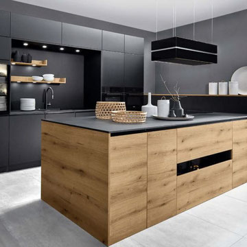 cuisine  bois et noire nouveauté  2020 avec ilot avec cuisson et hotte suspendue effet niche pour recevoir l'évier chez cuisine design Toulouse