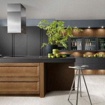 cuisine  bois et noire nouveauté  2020 avec ilot avec cuisson et évier sur le  plan de travail  de l'ilot et  espace repas pour 4 chez cuisine design Toulouse