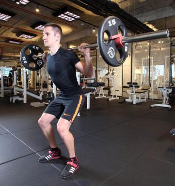 Der Elite-Radsportler und Duathlon-Weltmeister Tobias Eise zeigt das Ausführen der Kniebeuge mit der Langhantel