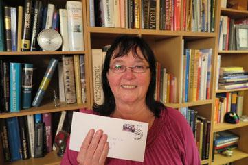 Elisabeth Streich zeigt stolz die Briefmarke mit zum CVJM-Jubiläum
