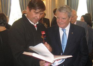 Bundespräsident Joachim Gauck (rechts) und Manfred Wille betrachten die Dokumentation zur Paddeltour zur deutschen Einheit 1990