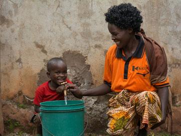 Eine Frau mit ihrem Sohn zapft Wasser aus einer Zisterne                  Foto: Kolpingwerk
