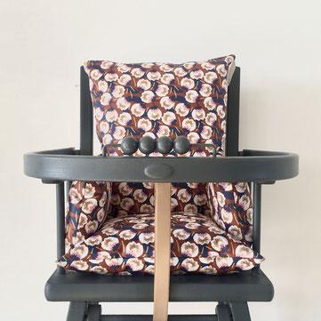 coussin de chaise haute universel présenté sur chaise haute combelle
